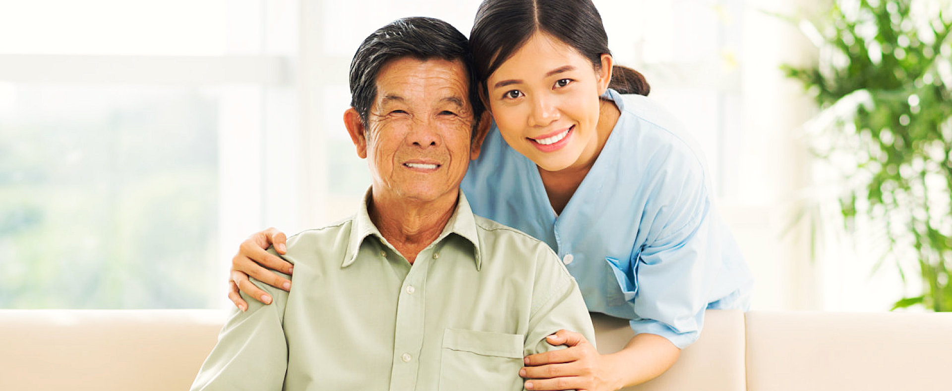 young lady caregiver and old man smiling