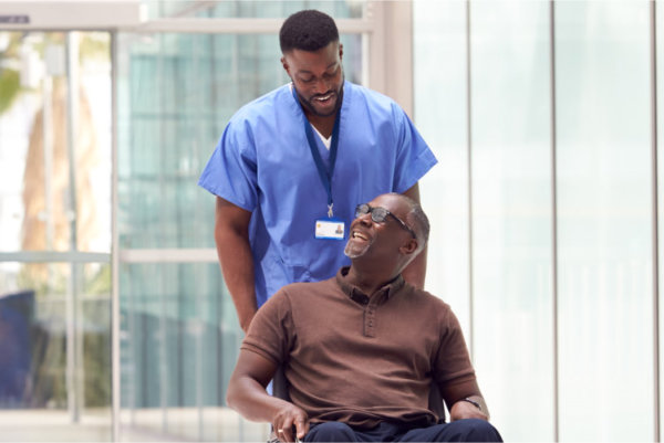 a male healthcare assisting the elderly man for his appointment